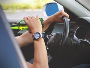 Person driving with a hand on the steering wheel and another one with a green bottle of beer