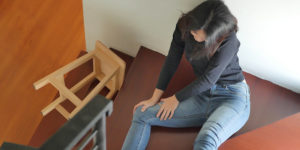 woman falling off the wooden stairs knee injury