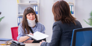 Woman with a neck injury filing a workers' compensation claim in an office