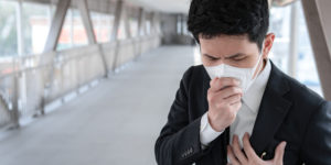Business man coughing in his workplace with a mask on