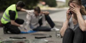 Desperate woman making a phone in a car crash scene