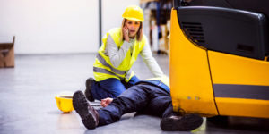 Man on the floor of his workplace and a woman calling for help next to him
