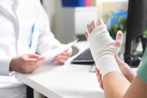 Person with an injured hand wrapped in a bandage talking to doctor. People who have suffered a serious injury usually feel the accident's rippling effects long after it occurred. It also doesn't help that their career and family life also suffers. Contact a Kansas personal injury attorney for any questions you may have.