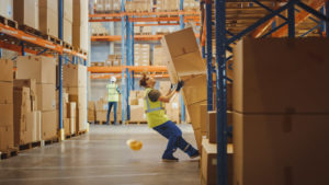 Warehouse worker unloading some boxes, falling back causing a work injury. Here's a look at the most common types of work injuries and what to do when you get injured in the workplace. It helps to consult with a Kansas workers' compensation attorney if you are injured on the job.