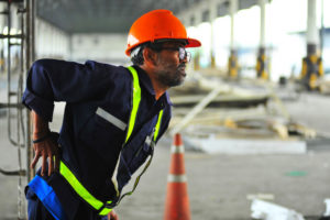 Construction worker supporting himself on his back due to injury. Getting medical treatment after being injured at work can be confusing for some people. Here are some handy tips to guide you, and you should not hesitate to consult with a Kansas workers' compensation attorney.